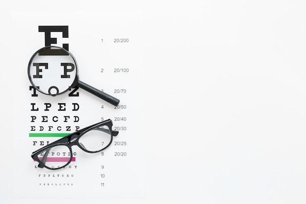 Tavolo alfabeto con lente d'ingrandimento e bicchieri Foto Gratuite