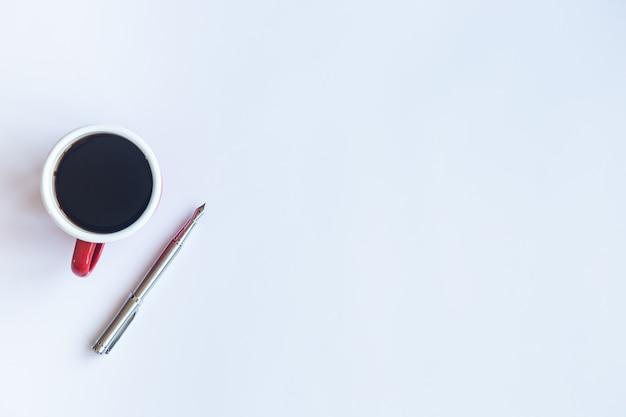 Tavolo bianco con penna e tazza di caffè Foto Premium