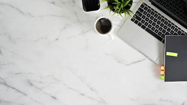 Tavolo bianco di marmo della scrivania della vista superiore con il computer portatile, la tazza di caffè e gli articoli per ufficio. Foto Premium
