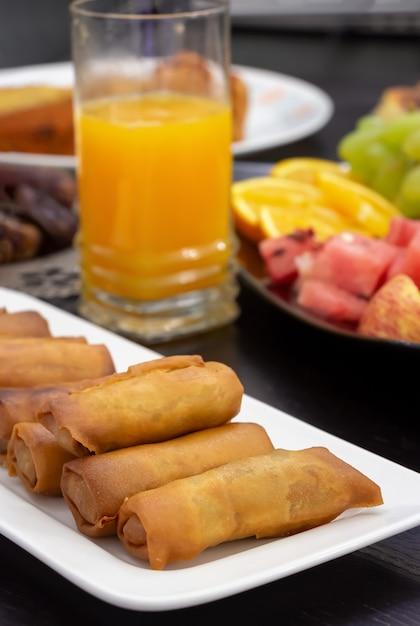 Tavolo buffet iftar. rotolo di primavera, frutta, succo d'arancia fresco, snack samosa, involtino primavera e frutta Foto Premium