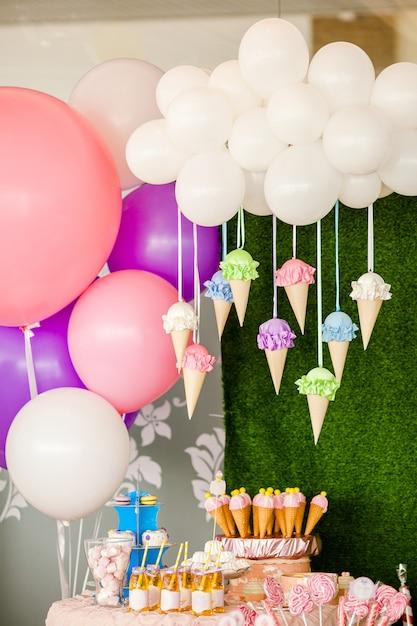 Tavolo con dolci e dessert, nuvola di palloncini e gelati e tanti palloncini colorati e grandi giocattoli di caramelle Foto Premium
