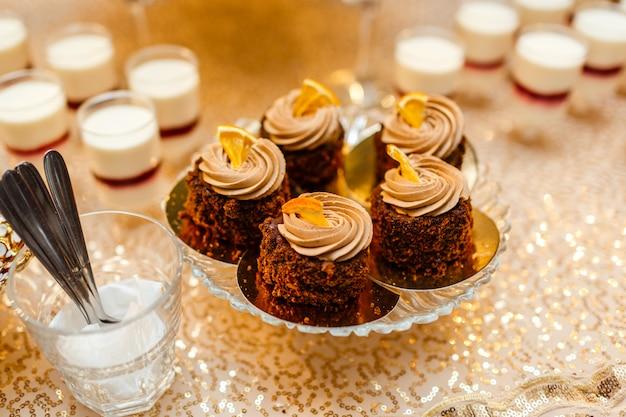 Tavolo con dolci e golosità per il ricevimento di nozze, tavolo da dessert decorato. deliziosi dolci a buffet di caramelle. tavolo da dessert per una festa. torte, cupcakes. Foto Premium