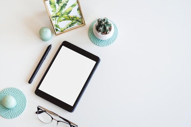 Tavolo con gadget mobile vicino a cornice, cactus, penna e occhiali da vista Foto Gratuite