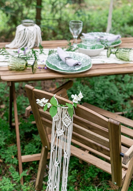Tavolo da pranzo di ricevimento di nozze di stile di boho con la tovaglia del macramè, decorazione su una tavola di legno rustica Foto Premium
