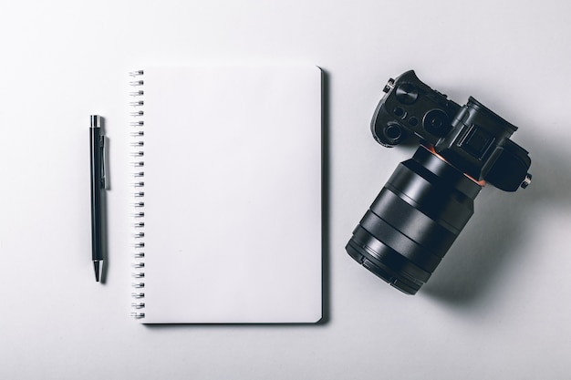 Tavolo da ufficio bianco con penna e fotocamera digitale mirrorless. Foto Premium
