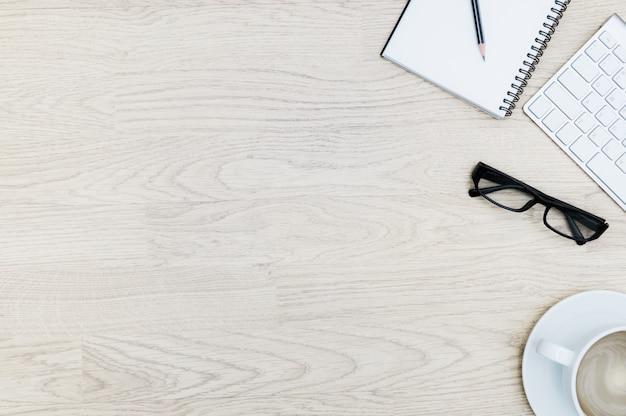Tavolo da ufficio con blocco note, mouse, tastiera, tazza di caffè, occhiali neri. vista dall'alto con design piatto laico aziendale Foto Premium