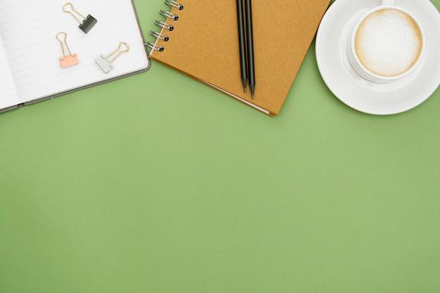 Tavolo da ufficio con taccuino e tazza di caffè. tabpe superiore, spazio di lavoro con spazio di copia. posa piatta creativa. Foto Premium