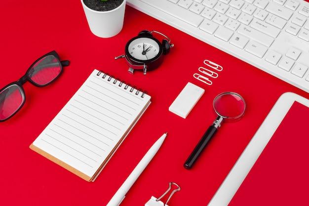 Tavolo da ufficio rosso con taccuino, tastiera e forniture vuoti. vista dall'alto con spazio di copia. disteso. Foto Premium