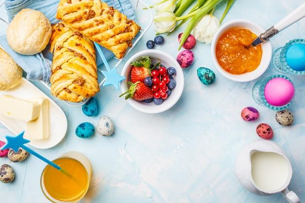 Tavolo della colazione di pasqua uova colorate, panini, succo e marmellata. sfondo blu, vista dall'alto, cornice alimentare. Foto Premium