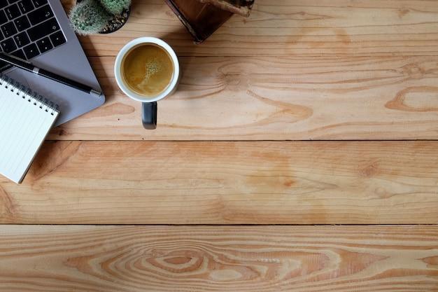 Tavolo di area di lavoro dell'ufficio con il computer portatile, il taccuino e stazionario sullo scrittorio di legno marrone. Foto Premium