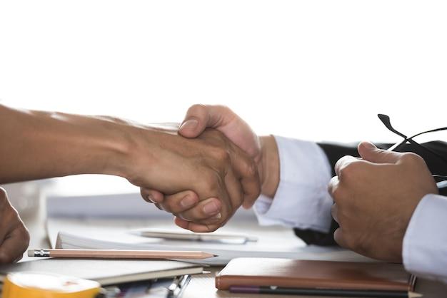 Tavolo di negoziazione, due uomini d'affari di successo stringono la mano come accordo. Foto Premium