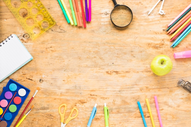Tavolo in legno con oggetti di disegno colorati intorno Foto Gratuite