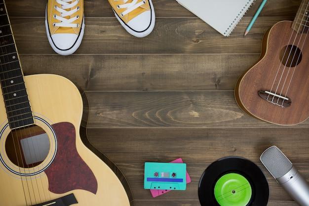 Tavolo in legno di compositore, chitarra, ukulele, quaderno, cassette audio, microfono, registratore Foto Premium