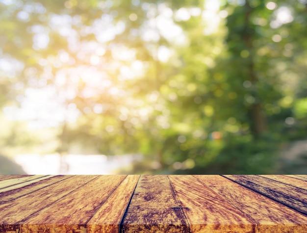 Tavolo in legno e immagine sfocatura dell'albero. Foto Premium