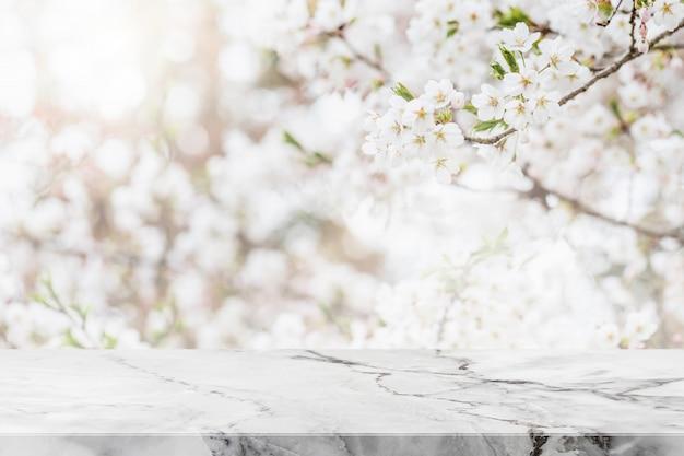 Tavolo in pietra di marmo bianco vuoto e albero fiore sakura sfocato sullo sfondo del giardino con filtro vintage - può essere utilizzato per visualizzare o montare i tuoi prodotti. Foto Premium