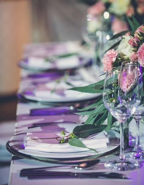 Tavolo per banchetti allestito con posate e fiori Foto Gratuite