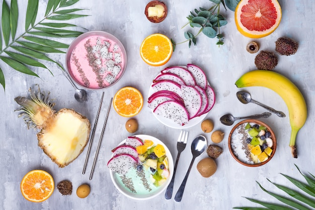 Tavolo per la colazione con ciotole di frullato di fragole di yogurt e frutta tropicale fresca su uno sfondo di pietra grigia. ciotola acai di frutti di bosco e fruttiera frullato, piatta laici Foto Premium