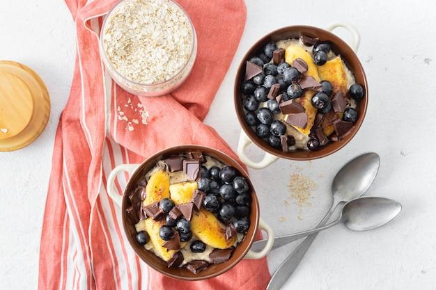 Tavolo per la colazione con farina d'avena piastra con banana fritta, cioccolato e mirtillo su una vista superiore bianca Foto Premium
