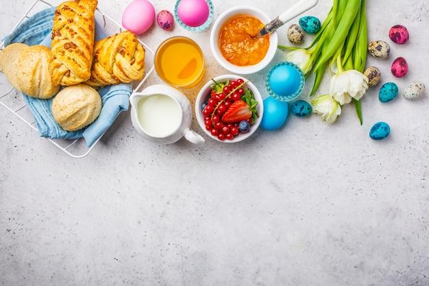 Tavolo per la colazione di pasqua, vista dall'alto. uova colorate, fiori, panini, latte, succo e marmellata, sfondo bianco. Foto Premium