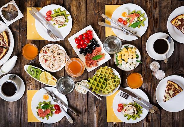 Tavolo per la colazione. set di brunch festivi, varietà di pasti con cialde di spinaci, salmone, formaggio, olive, involtini di pollo e cheesecake. vista dall'alto. disteso Foto Premium