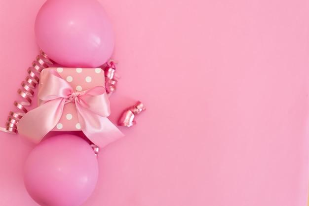 Tavolo rosa pastello con palloncini colorati e coriandoli per la vista dall'alto di compleanno. stile piatto laico Foto Premium