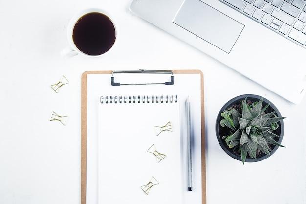 Tavolo scrivania da ufficio con computer, forniture, notebook, fiori e tazza di caffè Foto Premium