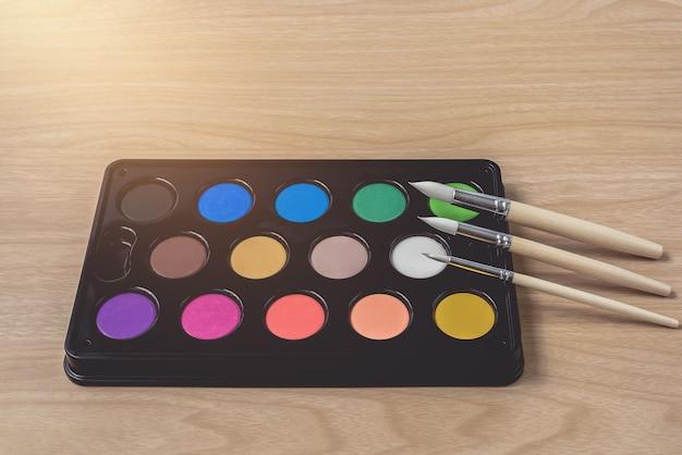 Tavolozza dell'acquerello e del pennello sulla tavola di legno marrone Foto Premium