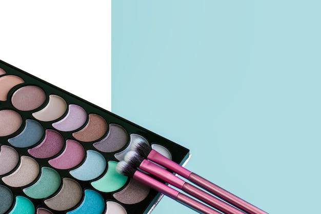 Tavolozza di trucco colorato con tre pennelli rosa su sfondo blu Foto Premium