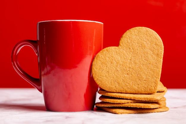 Tazza accanto a biscotti al cuore Foto Gratuite