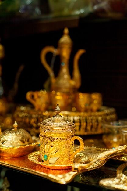 Tazza araba e teiera d'oro sul mercato orientale. tè orientale Foto Premium