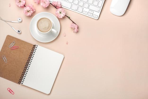 Tazza bianca con cappuccino, fiori di sakura, tastiera, sveglia, notebook su uno sfondo rosa pastello Foto Premium