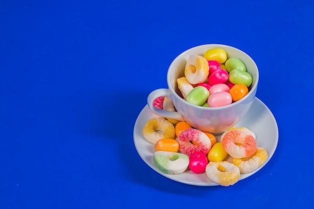 Tazza bianca con la caramella dolce isolata su fondo blu Foto Premium