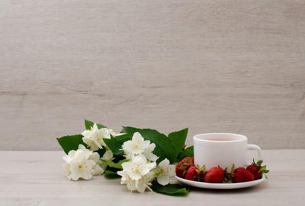 Tazza bianca con tè, un ramo di gelsomino e fragola Foto Premium