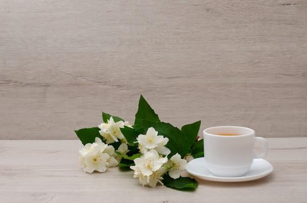Tazza bianca con tè, un ramo di gelsomino sul legno Foto Premium