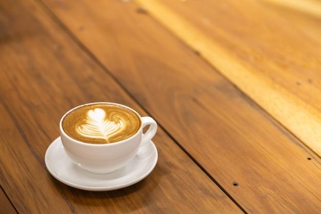Tazza bianca del latte caldo del caffè con arte del cuore e di forma del cuore sulla tavola di legno. Foto Premium
