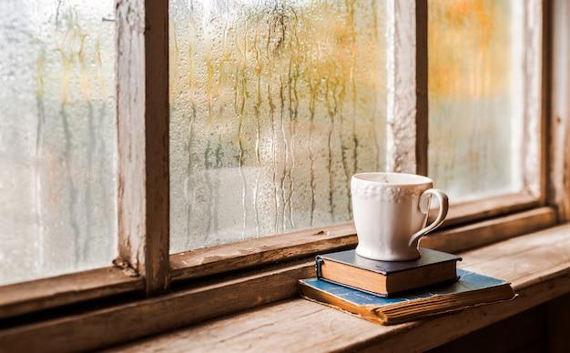Tazza bianca e libri antichi Foto Premium