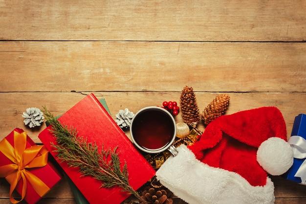 Libri Decorazioni Natalizie.Tazza Con Te Caldo Cappello Di Babbo Natale Regalo Decorazioni Natalizie Libri Su Uno Sfondo Di Legno Natale Vacanze Invernali Vista Piana Vista Dall Alto Foto Premium