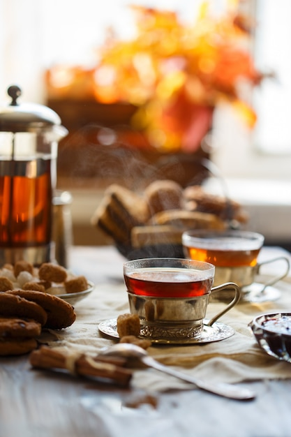 Tazza con tè caldo su una tavola su una delle foglie dell'arancia. concetto di casa accogliente Foto Premium
