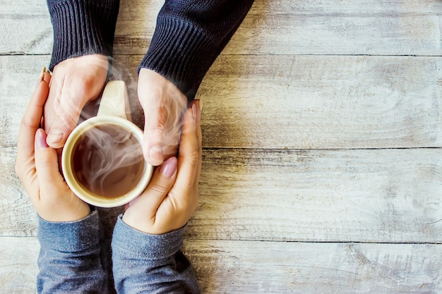 Tazza da bere per la colazione nelle mani degli innamorati. messa a fuoco selettiva Foto Premium