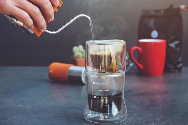 Tazza da caffè con filtro per caffeina e filtro a goccia. l'uomo rovescia l'acqua calda preparare il gocciolatore di vetro trasparente del caffè filtrato sulla tavola. vapore Foto Premium