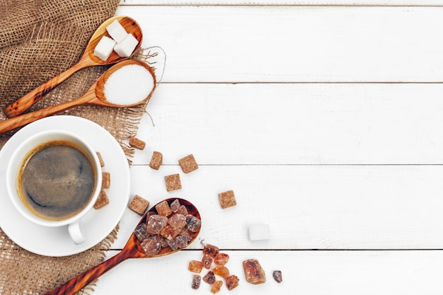 Tazza da caffè con le fette di zucchero sul fondo di legno della tavola Foto Premium