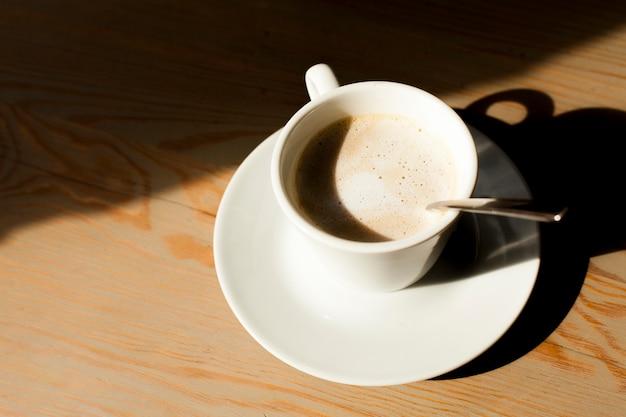 Tazza del caffè del latte con schiuma schiumosa su fondo di legno Foto Gratuite
