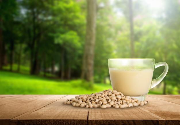 Tazza del latte di soia e fagiolo della soia con il fondo vago astratto della natura della foresta. Foto Premium