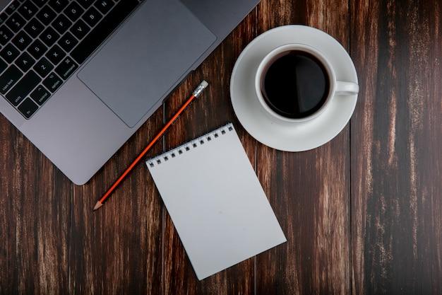 Tazza dello spazio della copia di vista superiore di tè con la matita e il taccuino del taccuino su fondo di legno Foto Gratuite