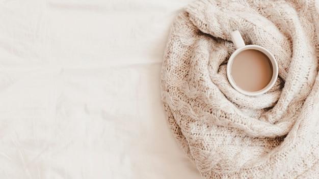 Tazza di bevanda calda in plaid sul lenzuolo Foto Gratuite