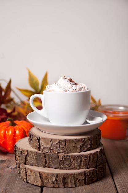 Tazza di cacao caldo cremoso con schiuma con foglie di autunno e zucche sullo sfondo Foto Premium