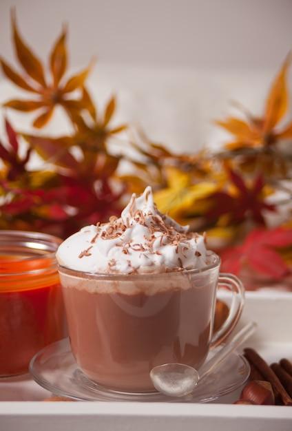 Tazza di cacao caldo cremoso con schiuma sul vassoio bianco con foglie di autunno e zucche sullo sfondo Foto Premium