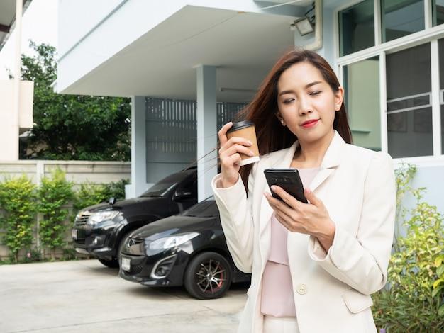 Tazza di caffè asiatica della tenuta della donna e smartphone usando mentre stando davanti alla casa. Foto Premium