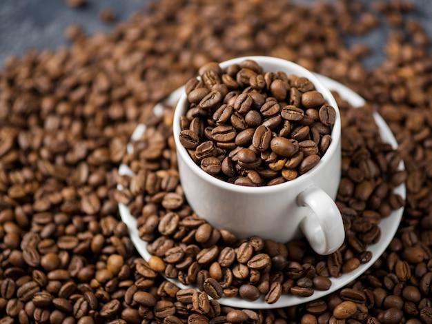Tazza di caffè bianca con chicchi di caffè Foto Premium