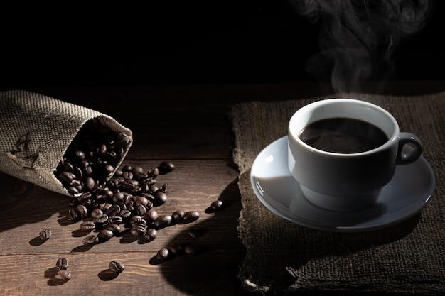 Tazza di caffè bianca e chicchi di caffè versati da de bag Foto Premium